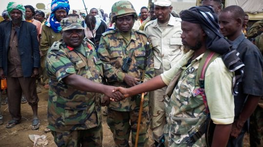 SOMALIA, Garsale: In a handout photograph dated 22 September and released by the African Union-United Nations Information Support Team 23 September, a senior commanding officer of the African Union Mission in Somalia (AMISOM) shakes hands with a commander of the Al Qaeda-affiliated militant group Al Shabaab after more than 200 fighters gave themselves up to AMISOM forces of the in Garsale, approximately 10km from the town of Jowhar, 80km north of the capital Mogadishu. The militants disengaged following in-fighting between militants in the region in which 8 Al Shabaab were killed, including 2 senior commanders. The former fighters were peacefully taken into AMISOM's protection handing in over 80 weapons in the process, in a further indication that the once-feared militant group is now divided and being defeated across Somalia. Deputy Force Commander of AMISOM Operations, Brigadier Michael Ondoga said a number of militants have contacted the AU force indicating their wish to cease fighting and that they their safety is assured if they give themselves up peacefully to AMISOM forces. AU-UN IST PHOTO / ABUKAR ALBADRI.